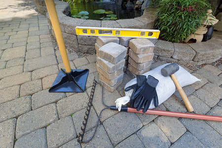 Picture of landscaper's tools. Tamper, rake, pavers, mallet, and level.