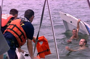 Coast Guard personnel retrieve people in the water after their boat capsized. Coast Guard photo by Chief Warrant Officer Jim Robertson.