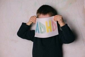 child holding an adhd sign