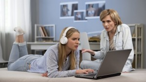 teen staring at laptop with headphones in while mom is trying to speak to her
