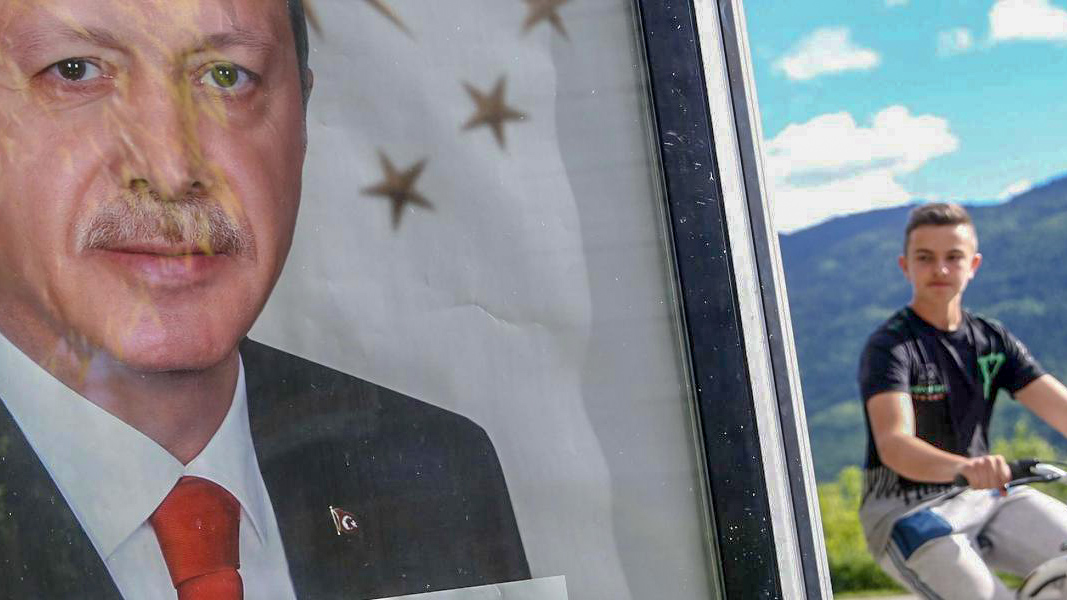 Photo: Cyclist glances at Portrait of Erdoğan.