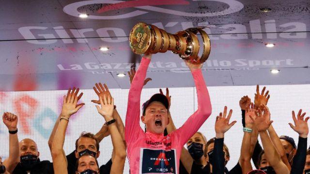 Tao Geoghegan Hart comemora a vitória no Giro d'Italia erguendo o troféu