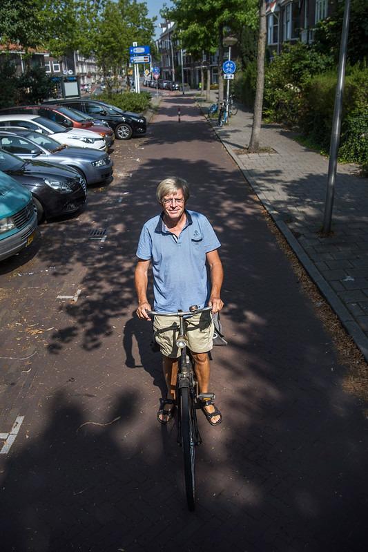 Jan Ploeger em sua bicicleta em uma ciclovia ladeada por calçamento e estacionamento de carros.