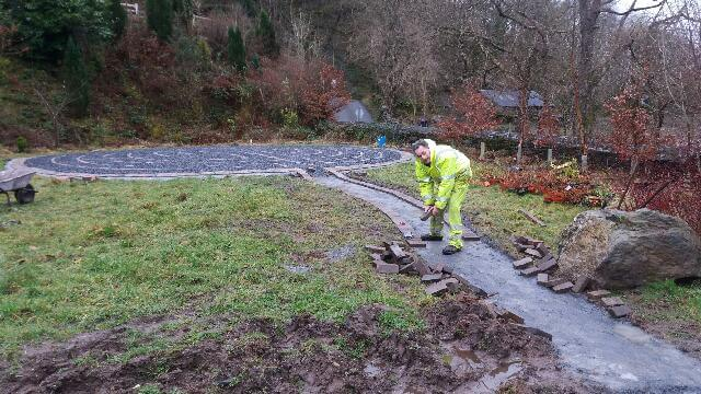 Path edging being installed (to be concreted in place when it stops raining, whenever that might be)