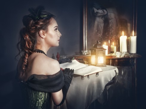 Woman with book in retro dress and ghost in the mirror