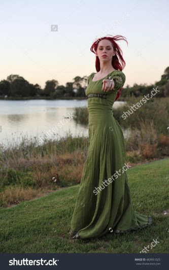 stock-photo-full-length-portrait-of-a-red-haired-beautiful-lady-wearing-a-green-medieval-gown-near-a-lake-483951025