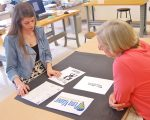 Rachel goes over some of her design ideas with Deb Meckley