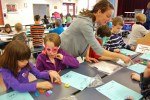 """Parent Vanessa Crowl helps students make words out of the phrase """"one hundred days."""""""