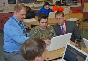 Teacher Kevin Bower, left, and state Rep. Ryan Aument, right, watch Masyn Jones demonstrate MySciLife.