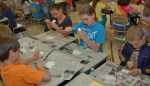 Third-graders try their hands at carving soap into fish shapes.