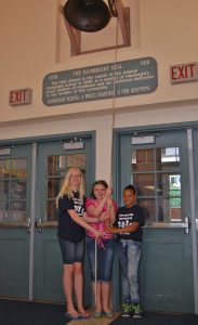 From left, Ashley Seiger, Delaney Mercado and Luz Agosto ring the Hambright bell.