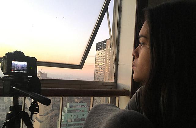 Na imagem, mulher olha por uma janela em que se vê diversos prédios