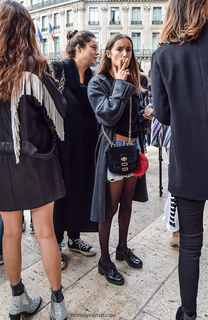 Paris street style fashion, how to wear grey longer coat, denim shorts with tights and cropped top. Bag with pompom