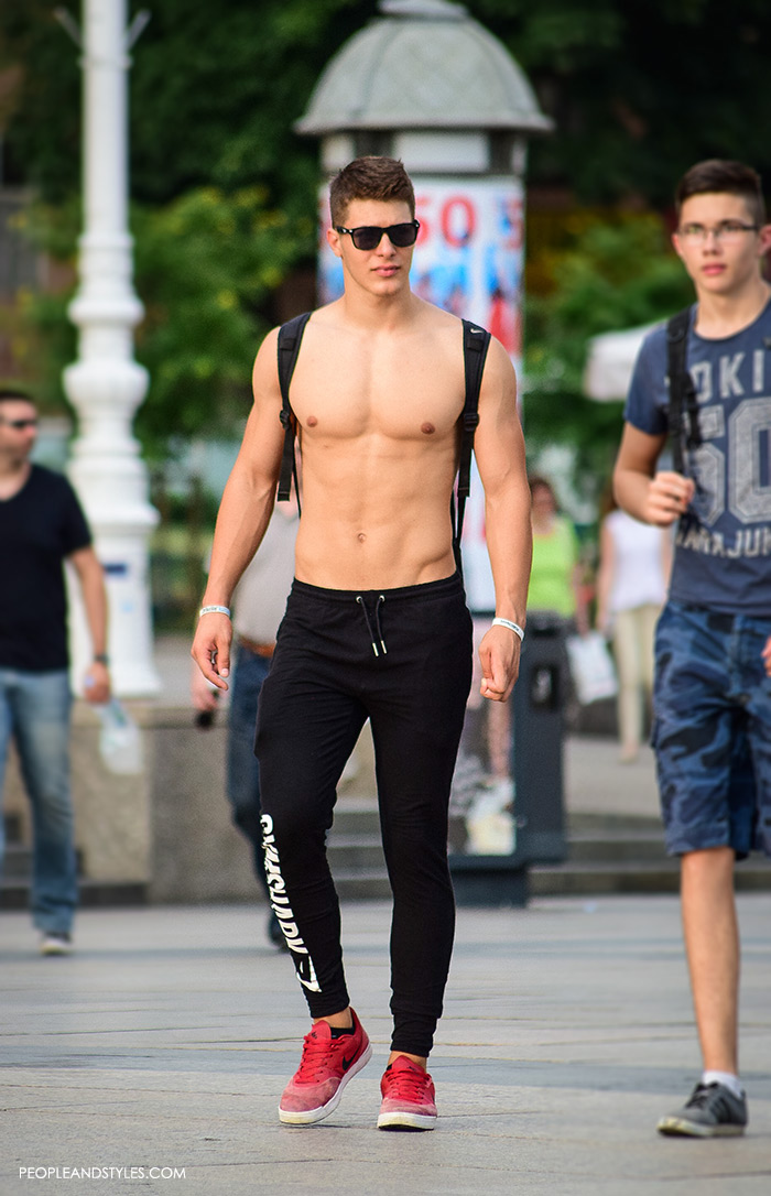 a guy wearing casual summet street fashion outfit shirless guy with joggers and red Nike sneakers