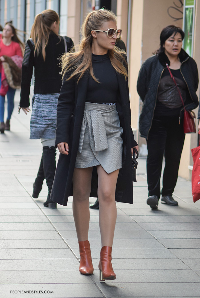This street stunner styled well her wrap mini skirt and ankle boots keeping the look elegant with a black clean line coat and a black bodysuit.