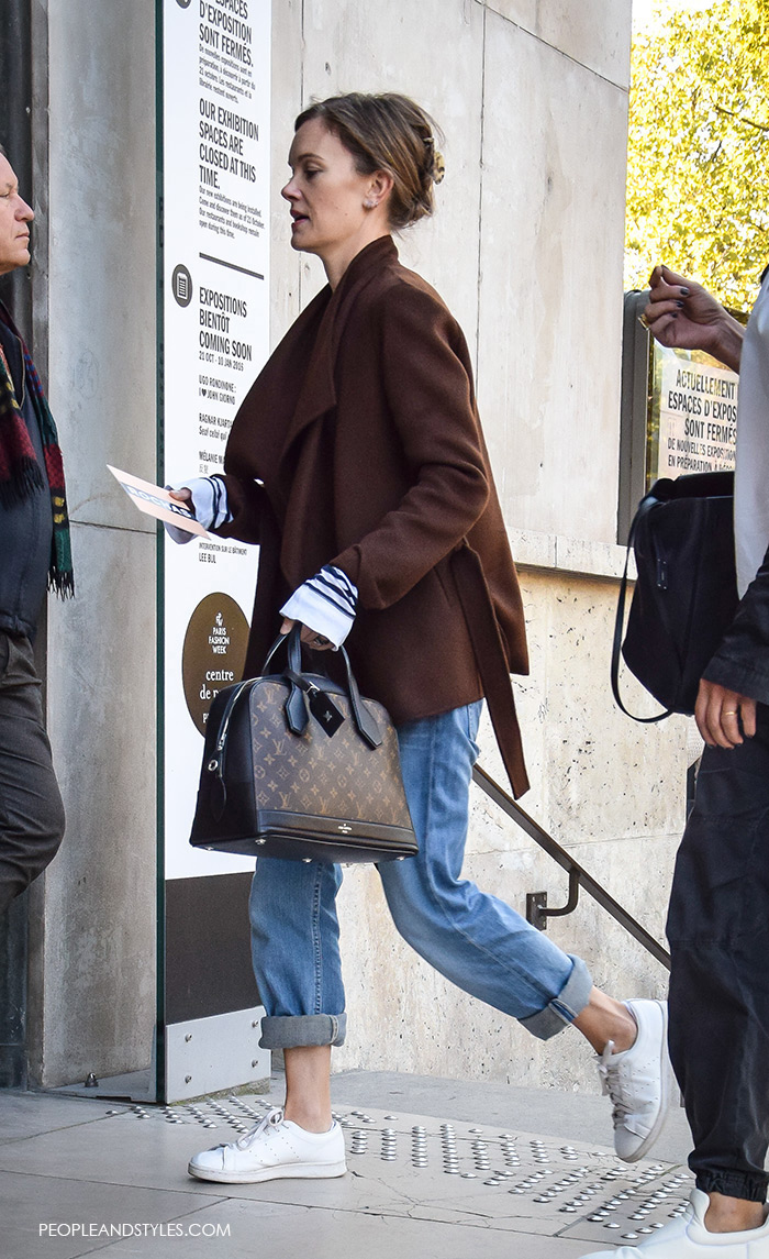 Jo Ellison, Financial Times fashion editor, How This Fashion Editor Wears White Sneakers, with Louis Vuitton bag, rolled up jeans, striped shirt and brown jacket