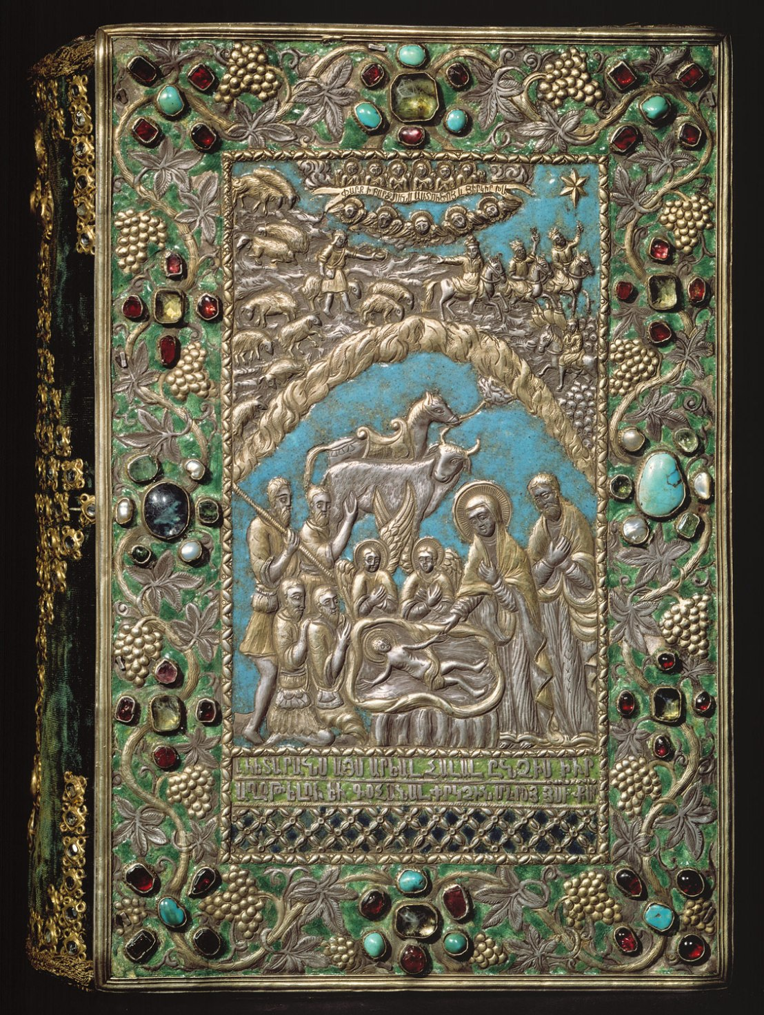 """This jeweled, enameled, and gilt-silver repoussé cover for a 13th century Armenian gospel is an examples of the work produced in the late seventeenth-century silversmith workshop of Kayseri. Both front and back cover are signed, informing us that they were made in Kayseri in 1691 by Astuatsatur Shahamir. The central image on the front cover depicts the Adoration of the Shepherds, and above, the magi following the star. Amid angels, the banner in the sky proclaims, """"Glory to God in the highest and on Earth peace."""" The cover was attached to a gospel copied and illuminated by a thirteenth-century scribe named Grigor, from Cilicia."""