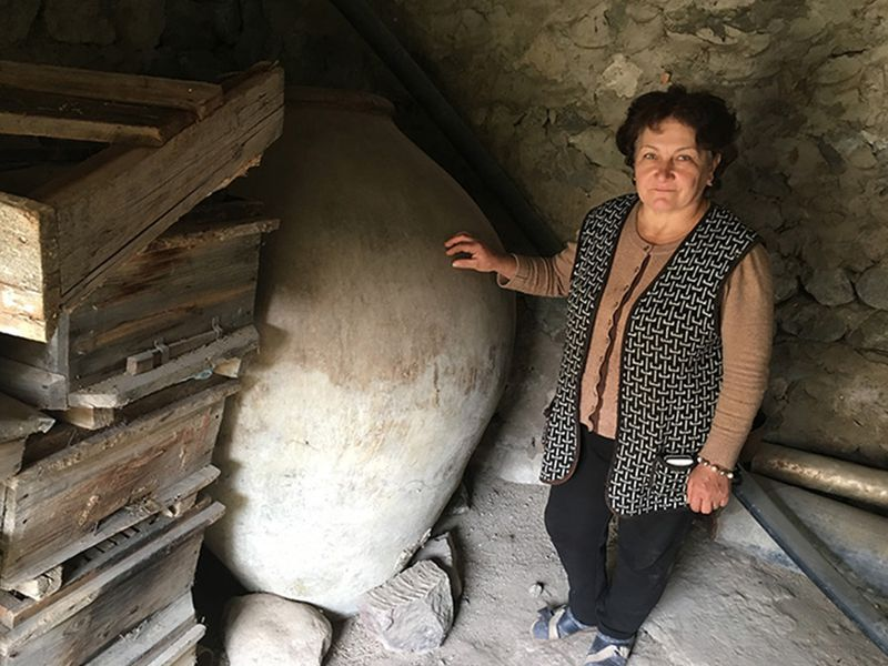 Asli Saghatelyan stands next to her father-in-law's 240-gallon karas, a clay vessel traditionally used in Armenia. (Photo by Karine Vann, Smithsonian)