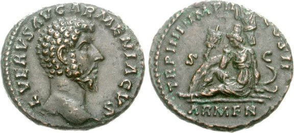 Left portrait of Lucius Verus AD 161-169, right: Armenia seated on the ground in attitude of mourning; in the background, shields, vexillum, and trophy.