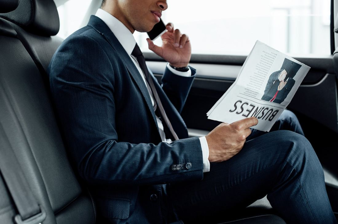 Businessman in limousine reading paper