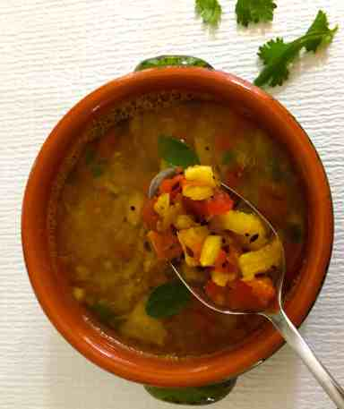 An orange bowl of pineapple rasam with a spoonful of pineapple and tomato pieces