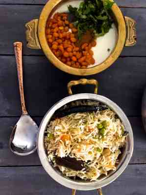 Matar ki Tehari from Eastern UP in India. A Pot of rice and peas cooked in spices, with a bowl of raita and a spoon alongside