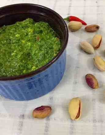 Parsely cilantro pesto in a blue bowl with pista nuts scattered nearby
