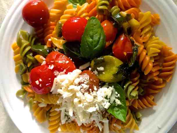 Colourful burst cherry tomatoes with coloured rotini pasta