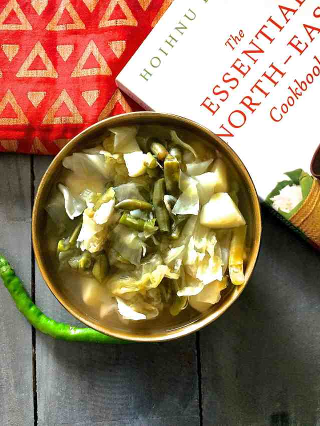 Oying vegetable stew from Arunachal Pradesh in a round brass bowl with a green chilli on one side, a red printed napkin and a cookbook alongside