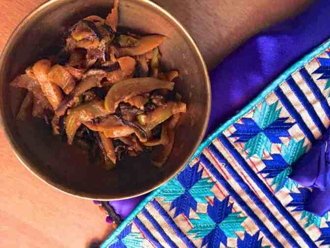 Kashmiri Green Apple Baingan Curry - a brass bowl of brinjal and apples cooked in spices, with a purple and blue silk jacket alongside