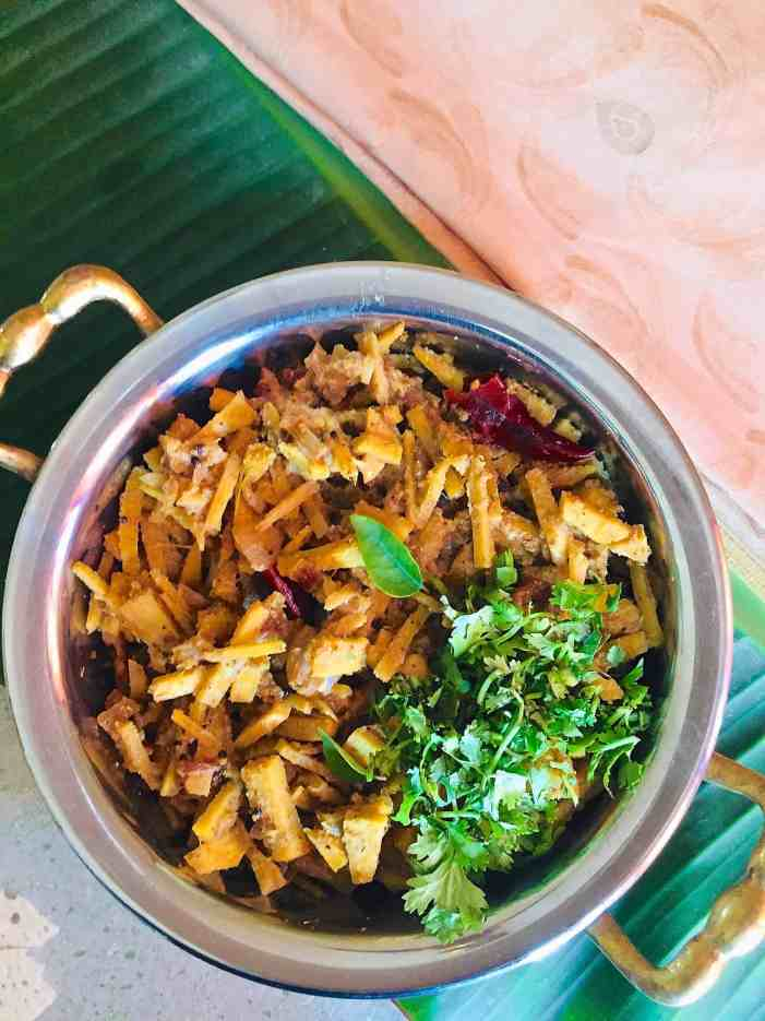 Bamboo shoot curry served in a brass bowl with garnish of coriander leaves, resting on a banana leaf with a pale pink mysore silk saree alongside