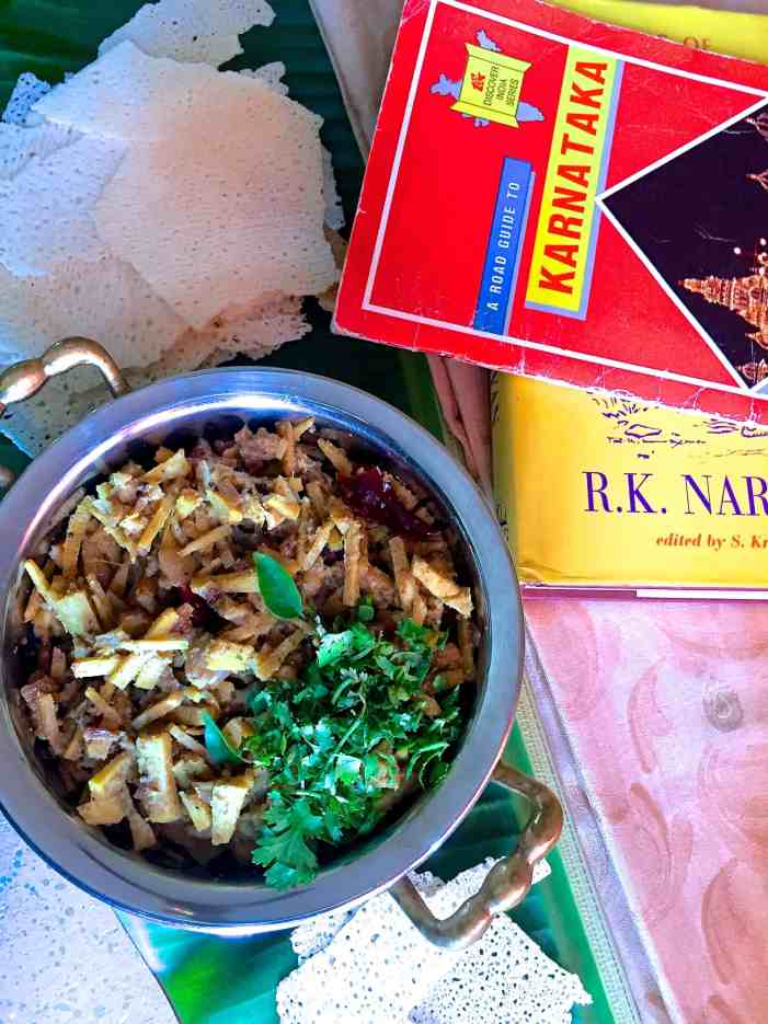 A bowl of bamboo shoot curry with a garnish of coriander leaves and with props showing the Karnataka theme- A guide book to Karnataka, a book by R K Narayanan who lived at Mysore, a Mysore silk saree