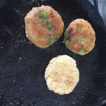 Aloo Tikki or Potato Patties being shallow fried in a little oil on a flat iron pan