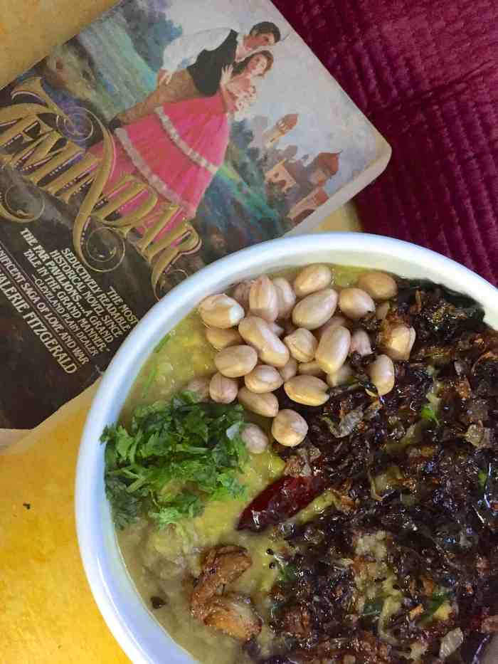 A white bowl with Arhar ki khatti Dal in the Lucknow style, garnished with peanuts and tempered with onions and garlic, and a novel based in Lucknow alongside