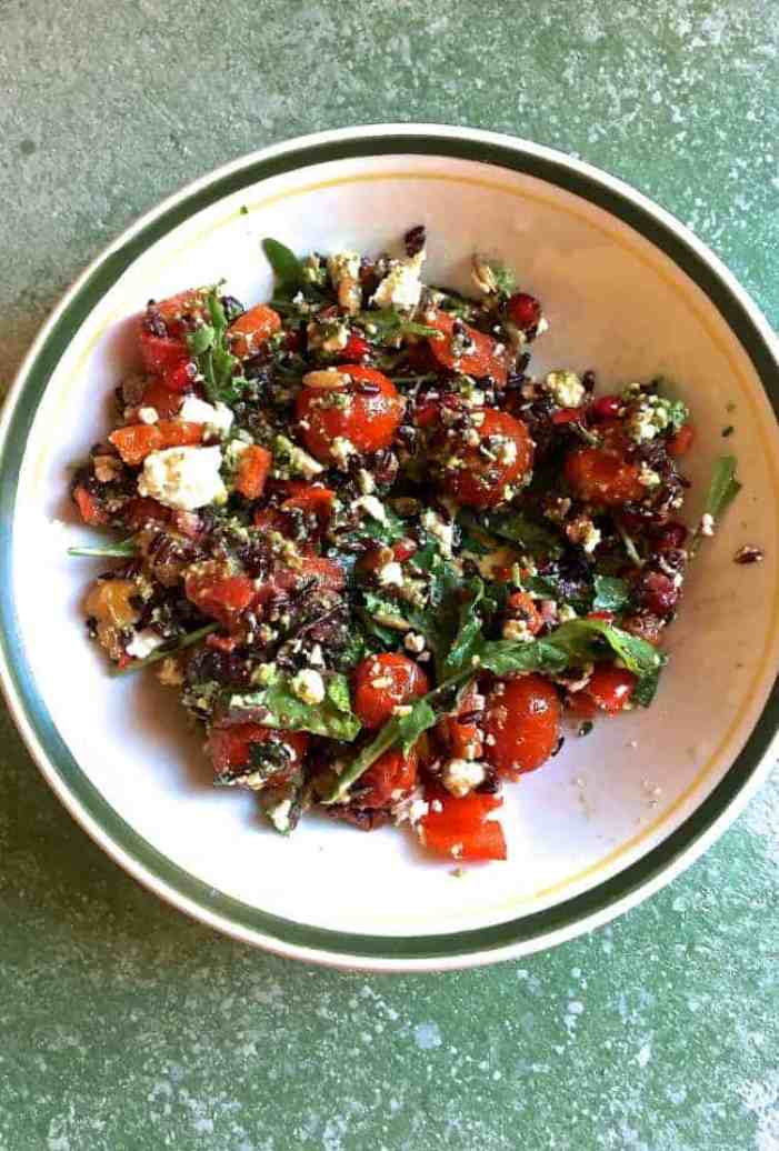 A green edged white plate with black rice, red and yellow cherry tomatoes, greens, goat cheese and seeds in a parsley pesto