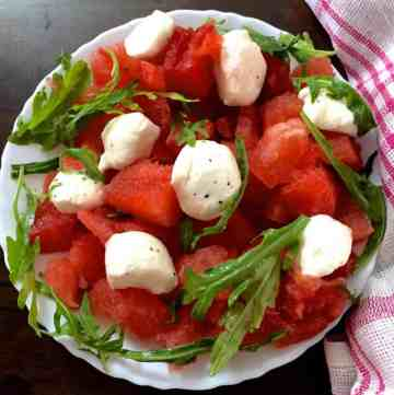 A white plate with a scalloped edge, filled with cubes of Watermelon and Halved Bocconcini cheese, with fresh arugula and pepper flakes for an easy cooling Watermelon Bocconcini Arugula Salad with Homemade Basil Oil