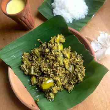 Green chunks of mixed vegetable curry in mustard paste and coconut, on a green piece of banana leaf resting on a clay plate. A clay tumbler in the bakcground with yellow mango lassi, white cooked rice on a banana leaf and a white hibiscus flower complete the presentation