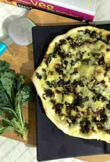 Thin crust Pizza on a black board, with kale and onion toppings. A bunch of kale to the left and a pizza cutter with a bright blue handle top left