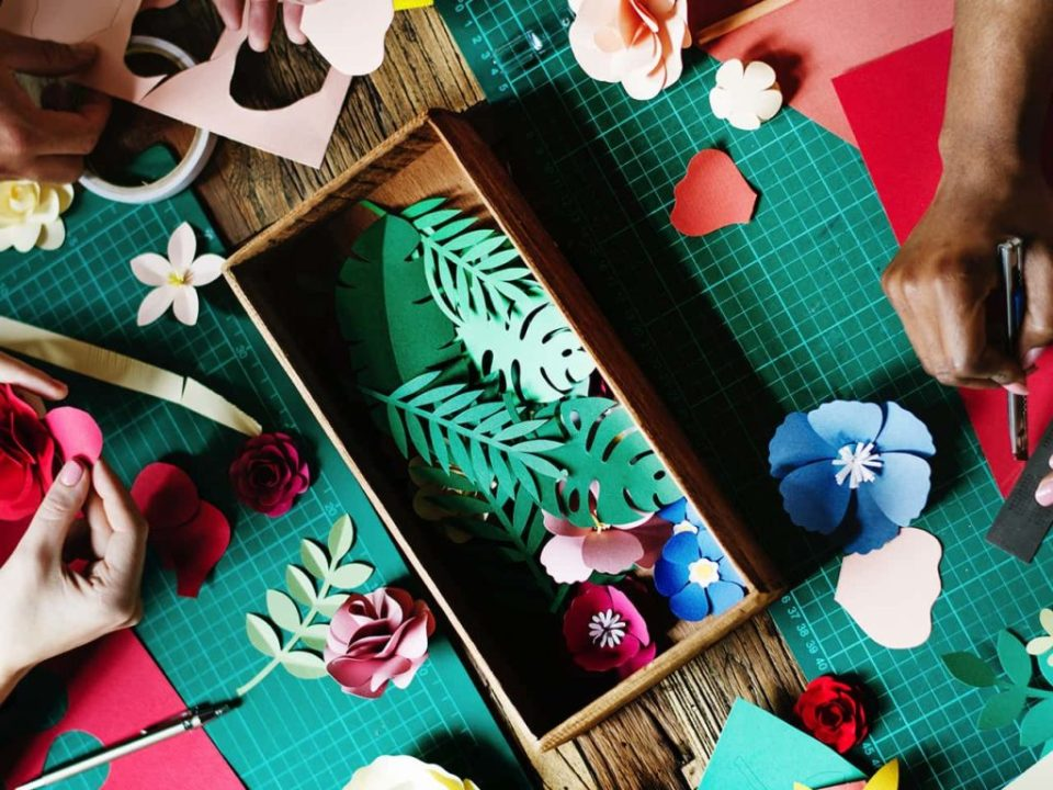 Closeup of two people making creative paper cutouts of leaves and flowers from paper and card