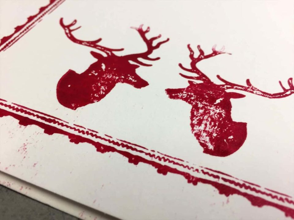 Closeup photograph of letterpressed christmas cards showing detail of printed reindeer in red ink on white card