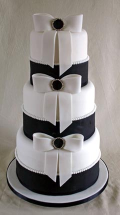 Amazing Black Wedding Cakes Three tier black and white wedding cake covered with white and black  fondant  Decorated with hand sculptured white bows sitting on top of each  tier and