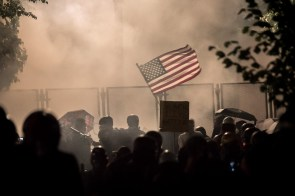 Teargas envelops the crowd of protesters.