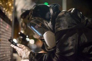 The information age - a protester in a gas mask checks his phone.