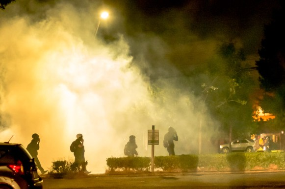 Protesters struggle through clouds of tear gas.