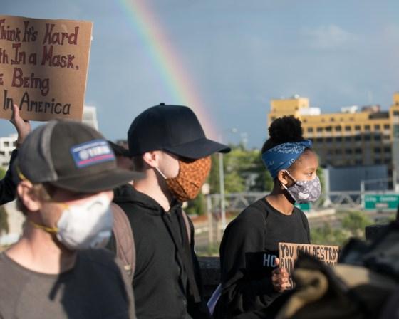 A rainbow frames a protest march.