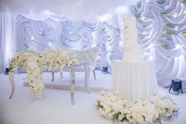 romantic wedding reception setup with clouds and lush flowers
