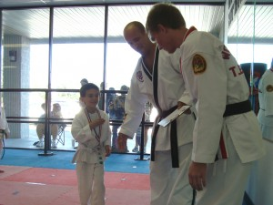 A Successful Tiny Tiger is rewarded with a medal and congratulations from his judges (Mr. Church, and World Champion T. Giddens)