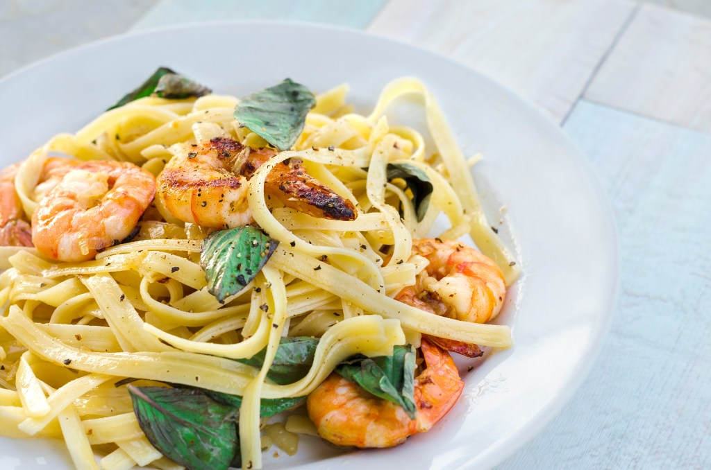 Pasta with prawns and basil leaves on white plate.