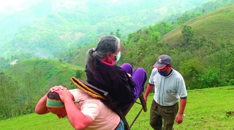 A la vieja usanza, un hombre transporta en una silla sujetada a su espalda, a una adulta mayor hacia el centro de vacunación en Tenango de Doria, en la región Otomí-Tepehua.