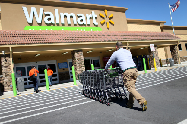 MIAMI, FL - FEBRUARY 19: Walmart employee Yurdin Velazquez pushes grocery carts at a Walmart store on February 19, 2015 in Miami, Florida. The Walmart company announced Thursday that it will raise the wages of its store employees to $10 per hour by next February, bringing pay hikes to an estimated 500,000 workers. (Photo by Joe Raedle/Getty Images)